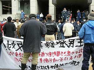 一方的記者会見に抗議する労働者