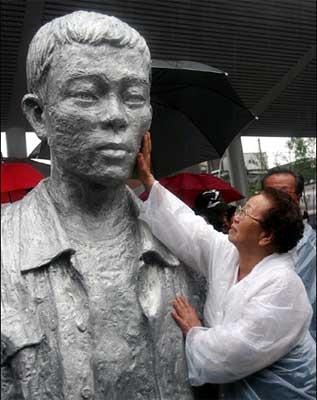 チョンテイルさんの彫像と母親のイ・ソソンさん