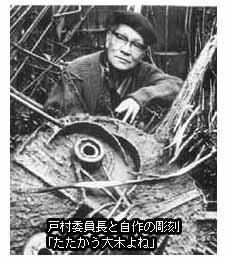 自作の彫刻「闘う大木よね」とともにカメラに収まる戸村一作反対同盟委員長