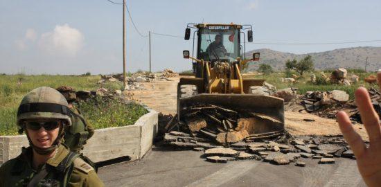 パレスチナの家屋を破壊するキャタピラー車のブルドーザー