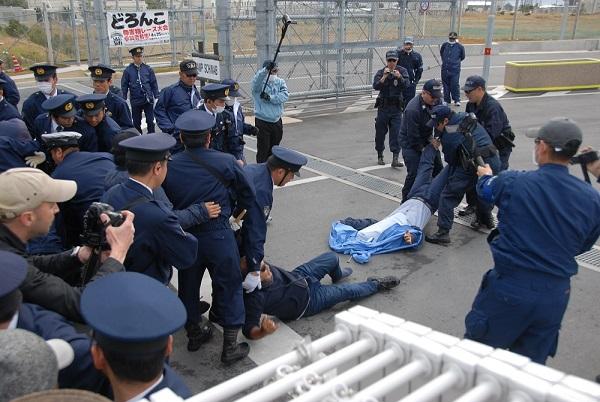 沖縄平和運動センターの山城博治議長(右)の足をつかみ、引きはがすシュワブ警備員ら=22日午前9時すぎ、名護市辺野古の米軍キャンプ・シュワブのゲート