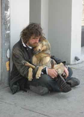 犬を抱くホームレスの写真
